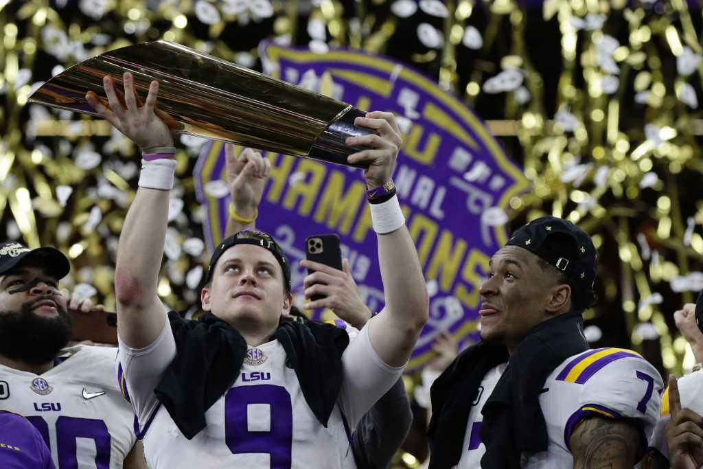 LSU quarterback Joe Burrow holds the trophy as safety Grant Delpit looks on after a NCAA College Football Playoff national championship game against C...