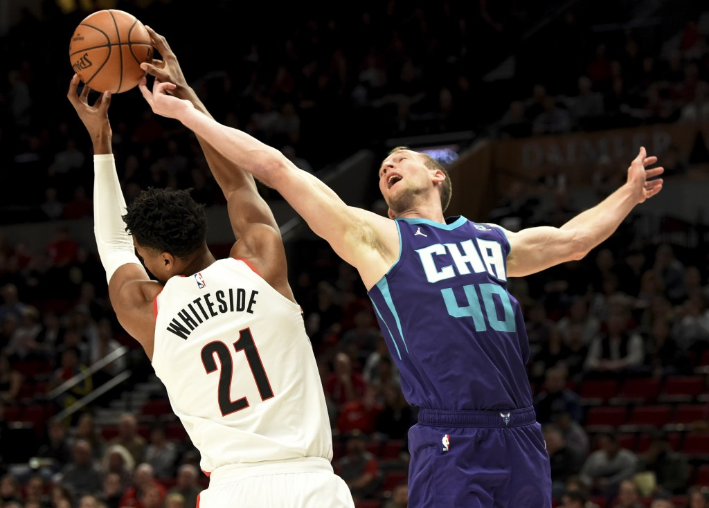 Portland Trail Blazers center Hassan Whiteside, left, grabs a rebound in front of Charlotte Hornets forward Cody Zeller, right, during the first half ...