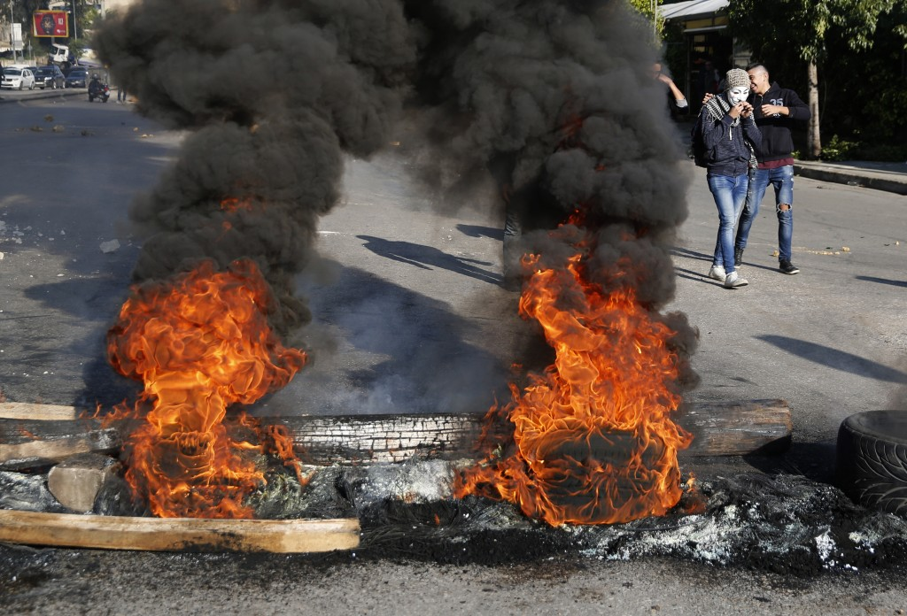 Anti-government protesters burn tires during ongoing protests after weeks of calm in Beirut, Lebanon, Tuesday, Jan. 14, 2020. Lebanon is facing its wo...