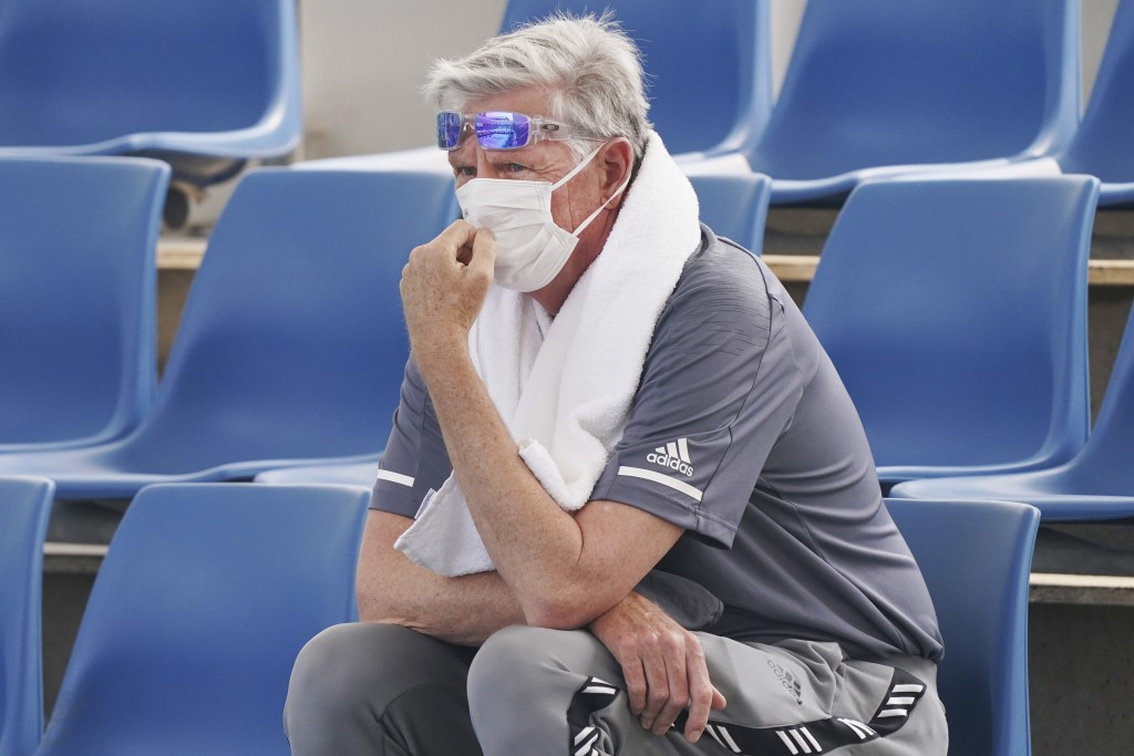 A spectator wears a mask as smoke haze shrouds Melbourne during an Australian Open practice session at Melbourne Park in Australia, Tuesday, Jan. 14, ...