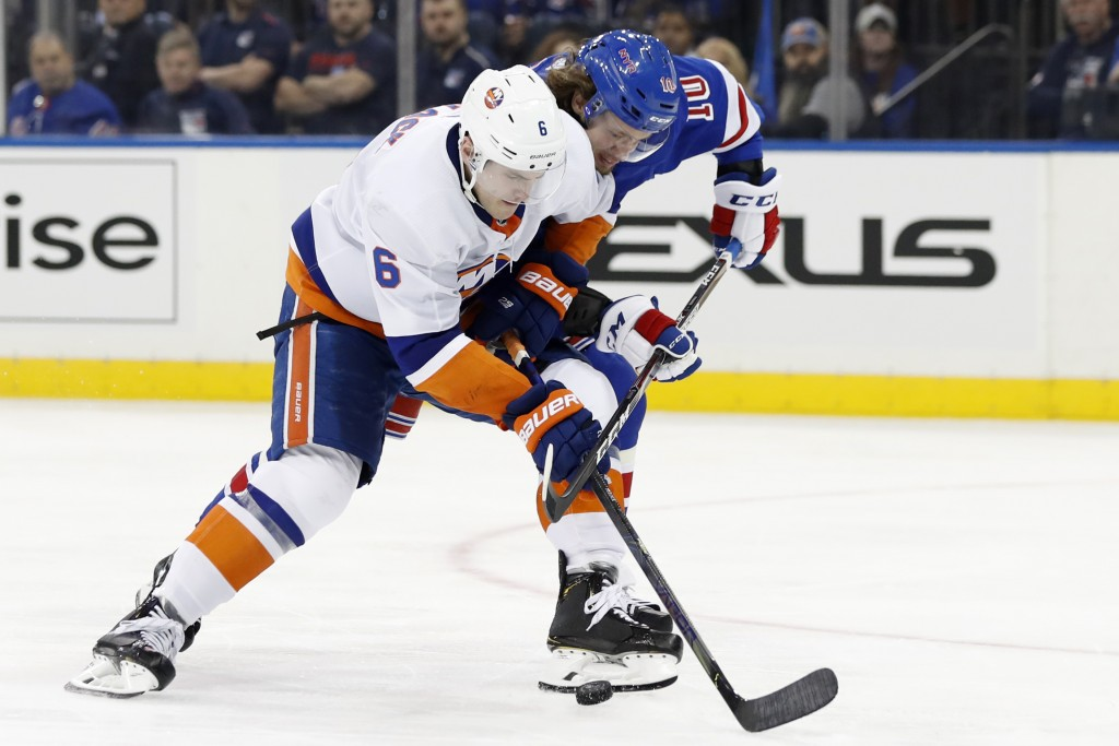 New York Islanders defenseman Ryan Pulock (6) tries to fend off New York Rangers left wing Artemi Panarin (10) during the second period of an NHL hock...