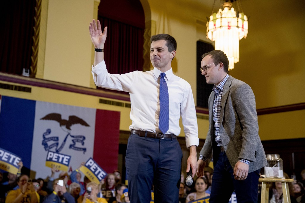 Democratic presidential candidate former South Bend, Ind., Mayor Pete Buttigieg, left, and his husband Chasten Buttigieg, right, stand onstage at a ca...