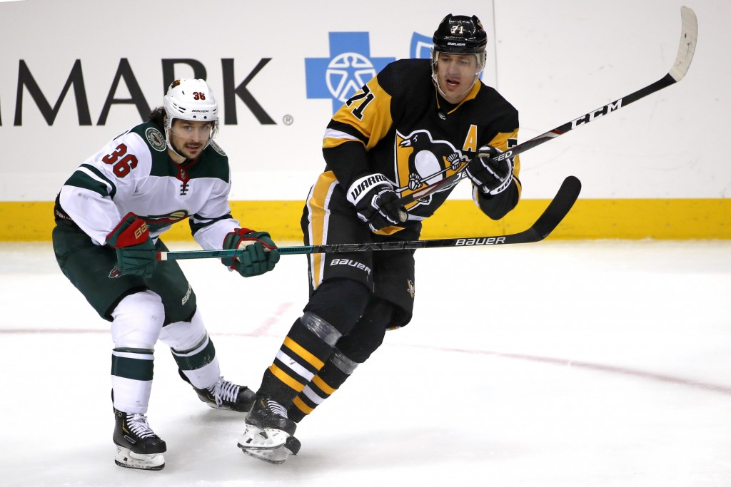 Pittsburgh Penguins' Evgeni Malkin (71) is defended by Minnesota Wild's Mats Zuccarello (36) during the first period of an NHL hockey game in Pittsbur...
