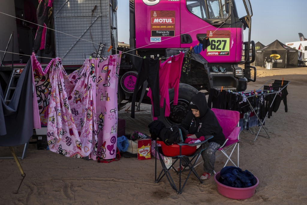 In this Monday, Jan. 13, 2020 photo, a team member of driver Camelia Liparoti, of Italy, and co-driver Annett Fischer, of Germany, does the laundry af...