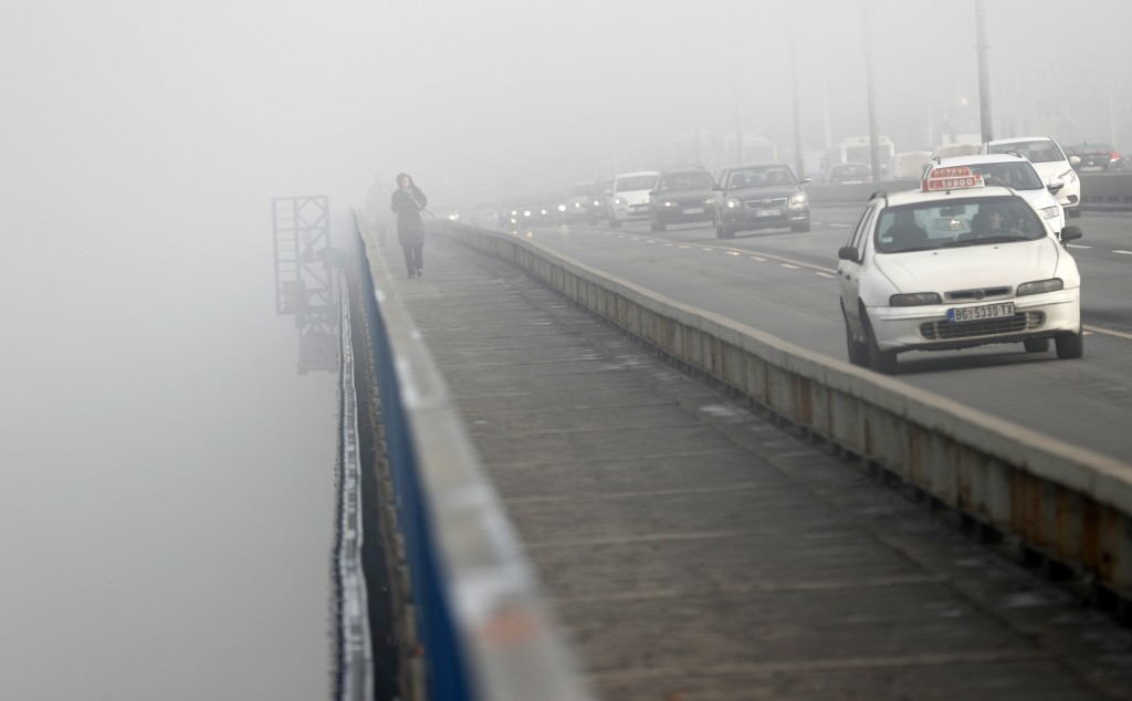 A girl walks across a bridge in Belgrade, Serbia, Wednesday, Jan. 15, 2020.  Serbia's government on Wednesday called an emergency meeting, as many cit...
