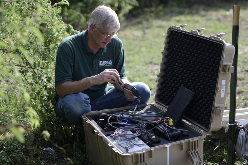 Thomas L. Pratt, a scientist with the United States Geological Survey, changes data cards in earthquake monitoring and recording equipment amid afters...
