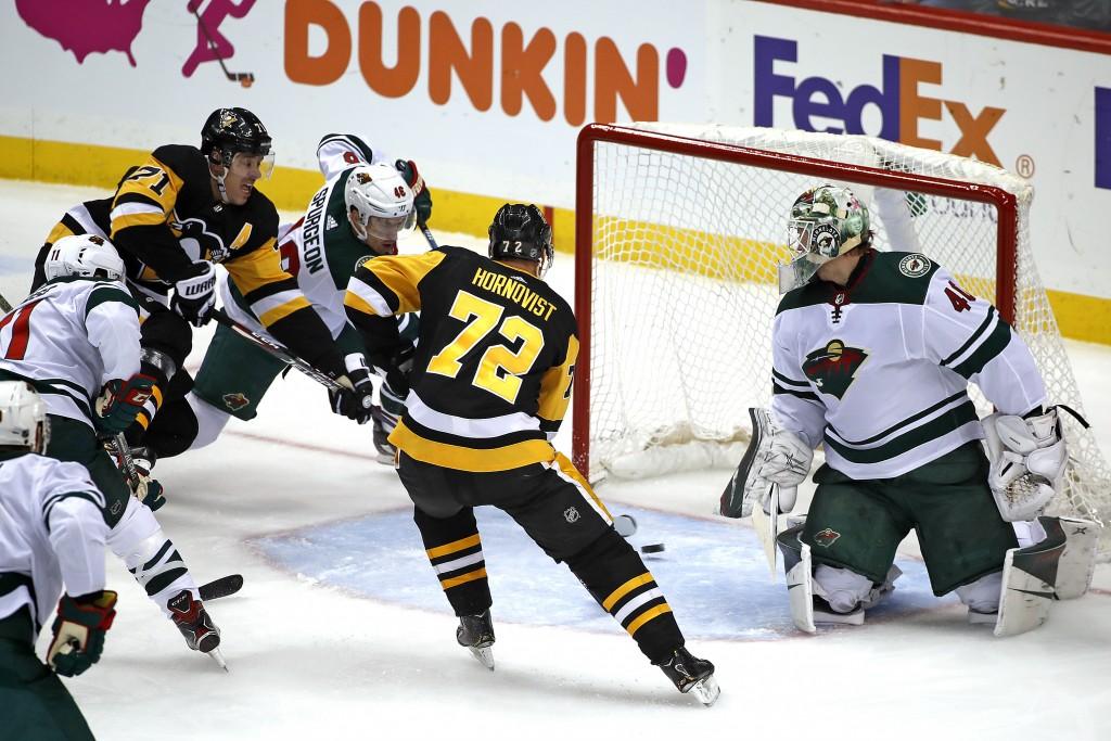 Pittsburgh Penguins' Evgeni Malkin (71) puts the puck behind Minnesota Wild goaltender Devan Dubnyk (40), with Jared Spurgeon (46) defending, for a go...