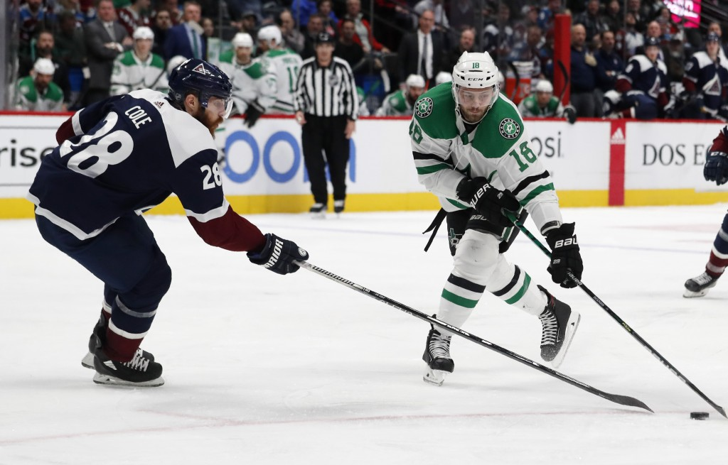 Dallas Stars center Jason Dickinson, right, reaches out to control the puck as Colorado Avalanche defenseman Ian Cole covers in the second period of a...