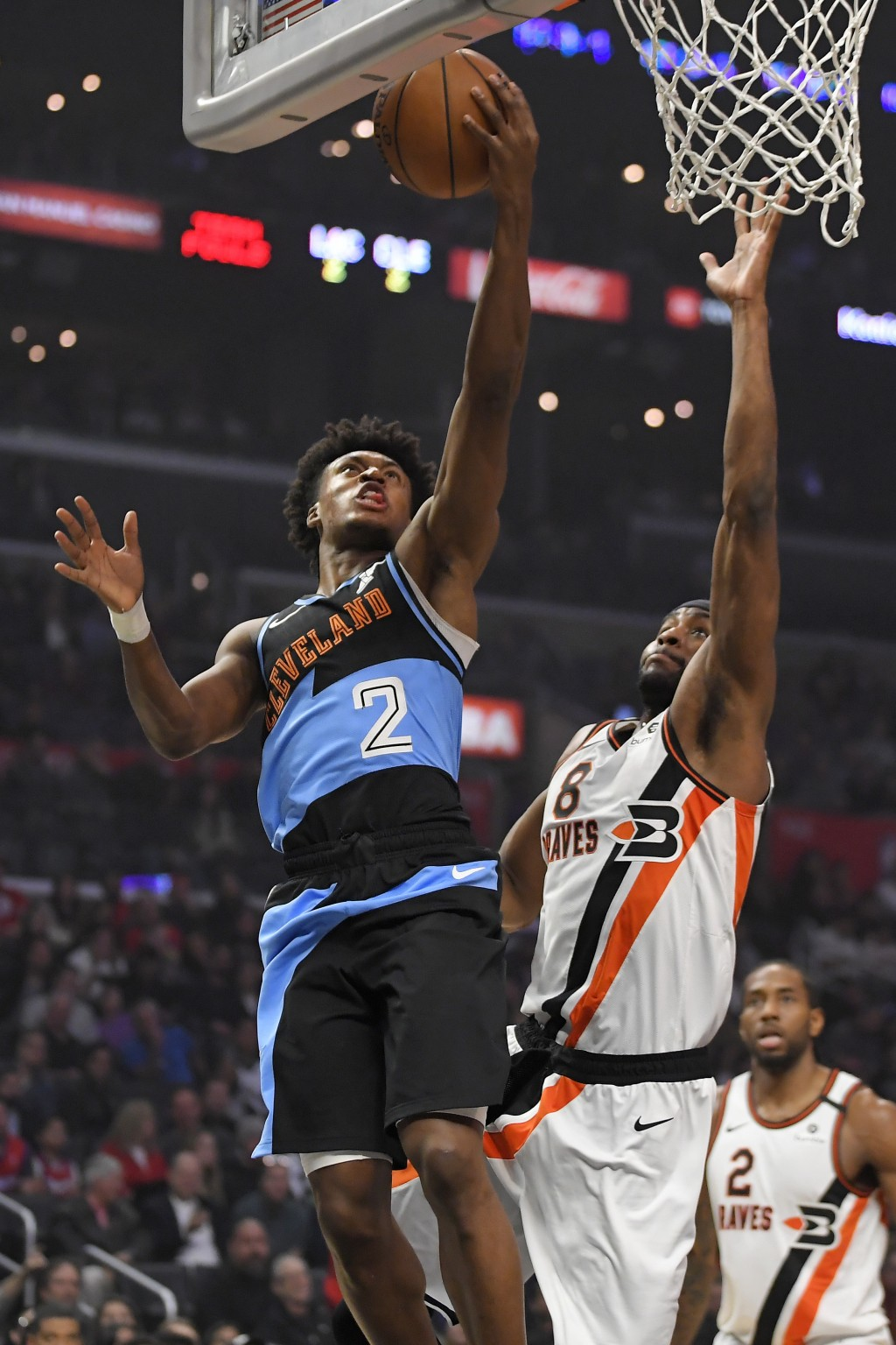 Cleveland Cavaliers guard Collin Sexton, left, shoots as Los Angeles Clippers forward Maurice Harkless, center, defends while forward Kawhi Leonard wa...