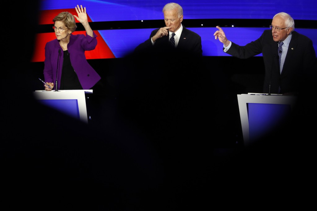 Democratic presidential candidate Sen. Elizabeth Warren, D-Mass., and Sen. Bernie Sanders, I-Vt., seek to answer a question as Joe Biden pauses Tuesda...