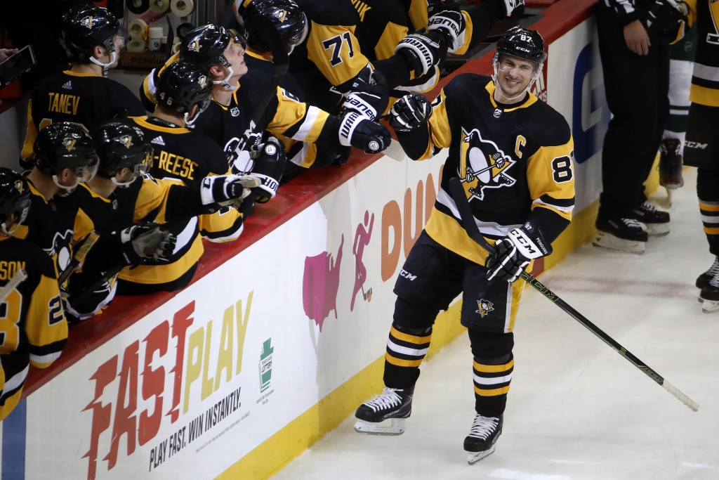 Pittsburgh Penguins' Sidney Crosby (87) returns to the bench after his goal during the third period of an NHL hockey game against the Minnesota Wild i...