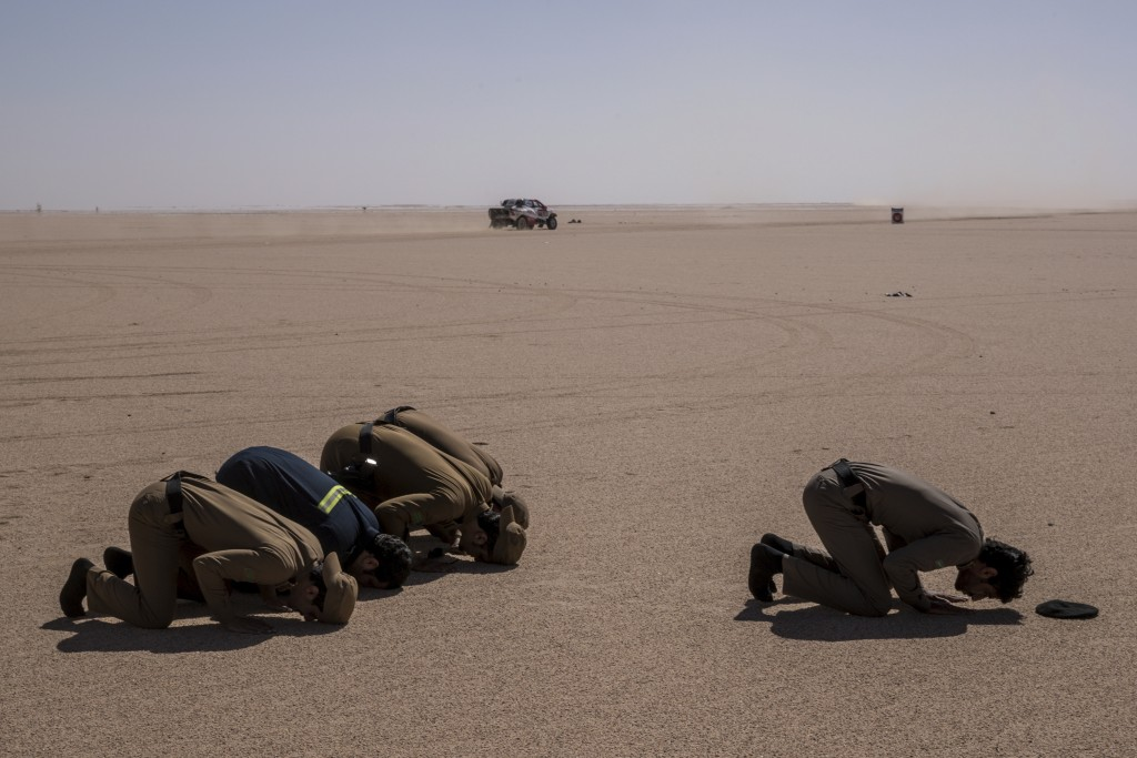 In this Sunday, Jan. 12, 2020 photo, Saudi Arabia security forces pray while a care races during stage seven of the Dakar Rally between Riyadh and Wad...