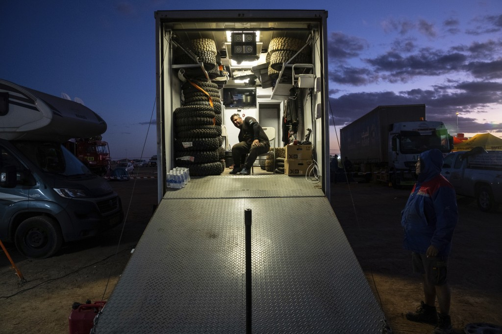 In this Thursday, Jan. 9, 2020 photo, a team staffer pauses at the bivouac after stage five of the Dakar Rally in Hail, Saudi Arabia. Formerly known a...
