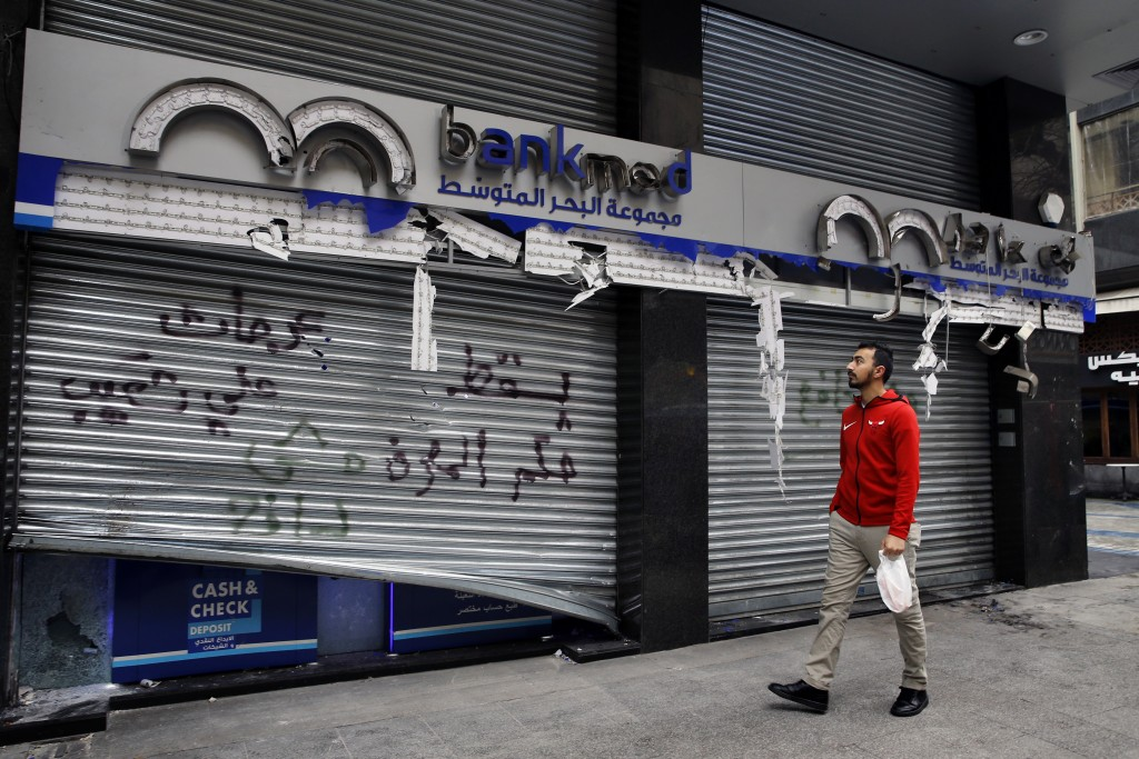 "A man passes by the broken facade of the Bank MED that was smashed by anti-government protesters with a message that reads in Arabic, ""Down with the r..."