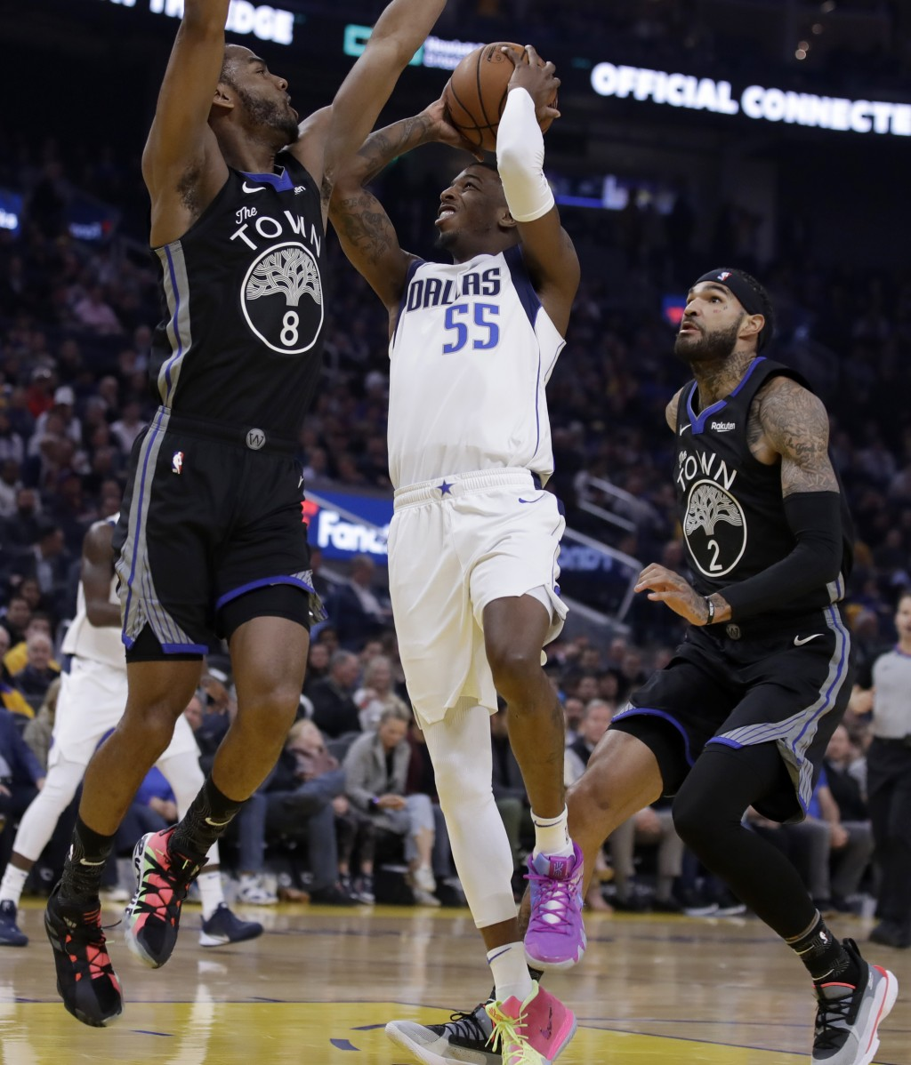 Dallas Mavericks' Delon Wright, center, shoots between Golden State Warriors' Alec Burks, left, and Willie Cauley-Stein (2) in the first half of an NB...