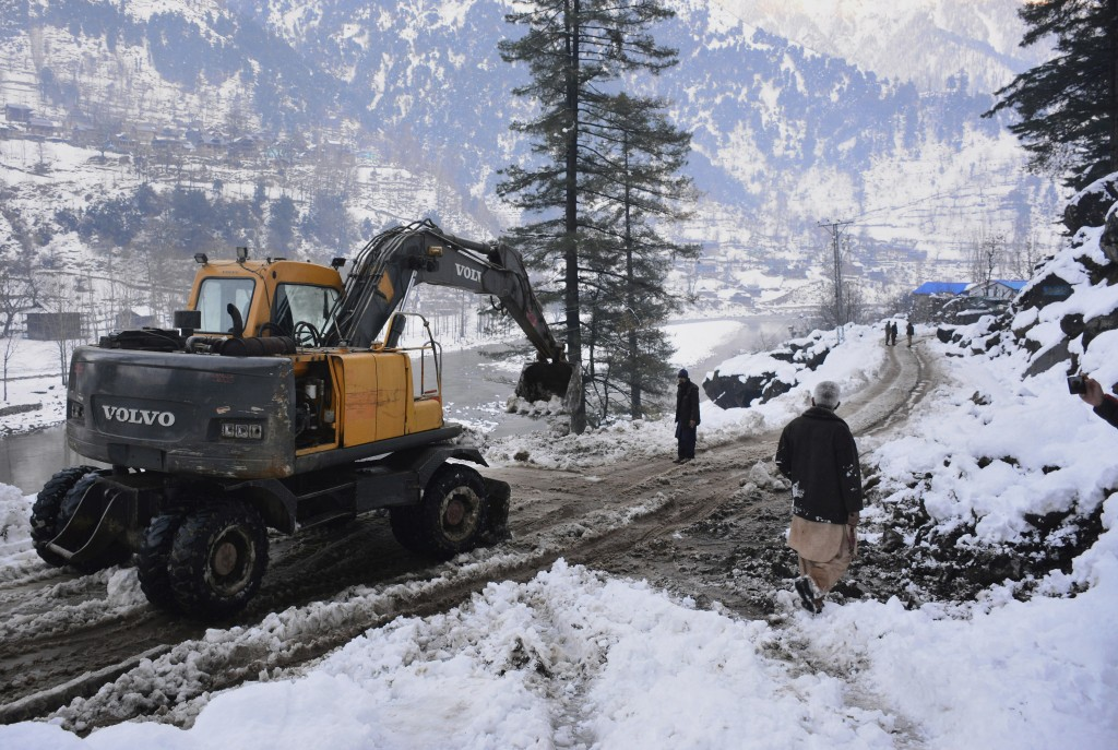 Workers with heavy machinery clear a snow-covered road in Keran, a small town in Neelum Valley, Pakistan-administered Kashmir, Tuesday, Jan. 14, 2020....