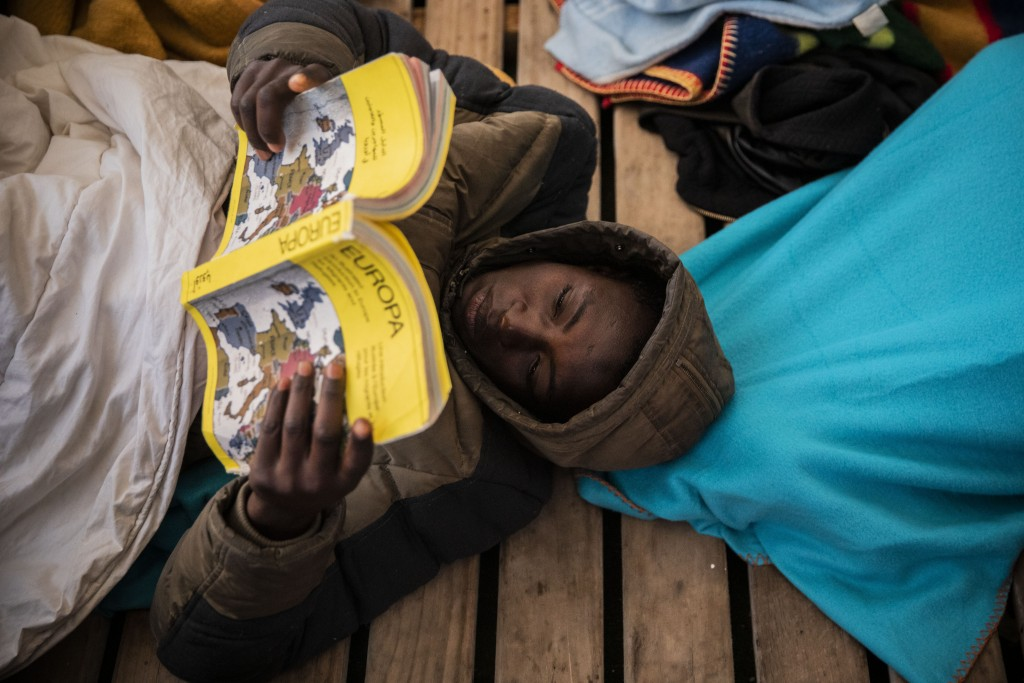 In this Sunday Jan. 12, 2020 photo, Gauro, 15, from Mali, reads a book aboard the Open Arms rescue vessel as the ship sails north with 118 people from...