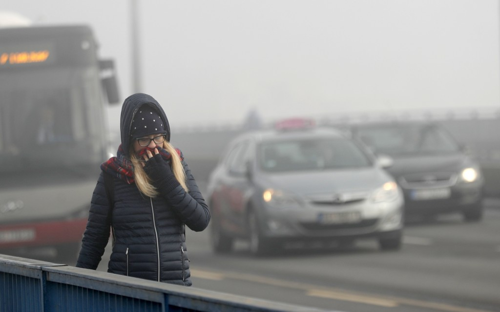 A girl walks across a bridge in Belgrade, Serbia, Wednesday, Jan. 15, 2020. Cities throughout the Balkans have been hit by dangerous levels of air pol...