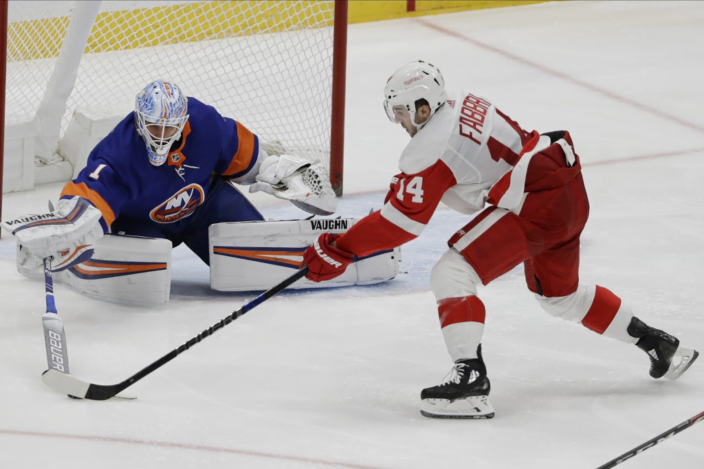 New York Islanders goaltender Thomas Greiss (1) poke checks Detroit Red Wings' Robby Fabbri (14) during the third period of an NHL hockey game Tuesday...