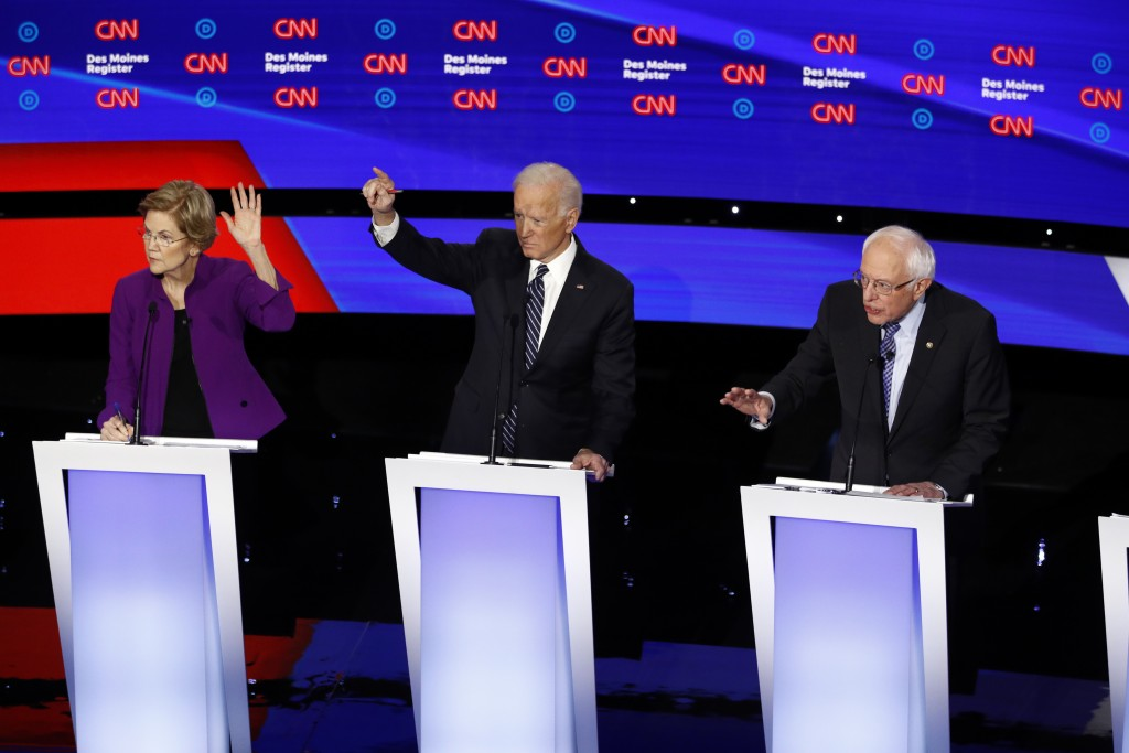 From left, Democratic presidential candidate Sen. Elizabeth Warren, D-Mass., and former Vice President Joe Biden raise their hands as candidate Sen. B...
