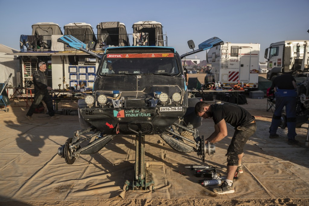 In this Monday, Jan. 13, 2020 photo, a mechanic works on a car after stage eight of the Dakar Rally in Wadi Al Dawasir, Saudi Arabia. Formerly known a...