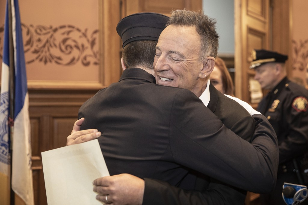 In this photo provided by the Jersey City Mayor's Office, Bruce Springsteen hugs his son Sam Springsteen after he is sworn in as a Jersey City Firefig...