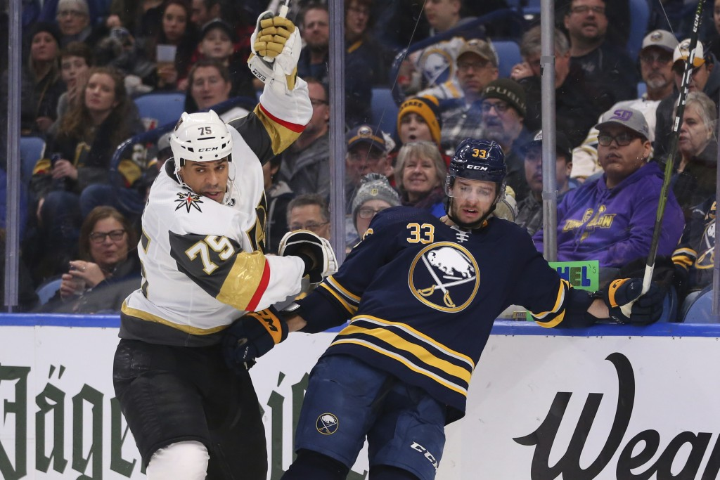 Buffalo Sabres defenseman Colin Miller (33) and Vegas Golden Knights forward Ryan Reaves (75) colllide behind the net during the second period of an N...