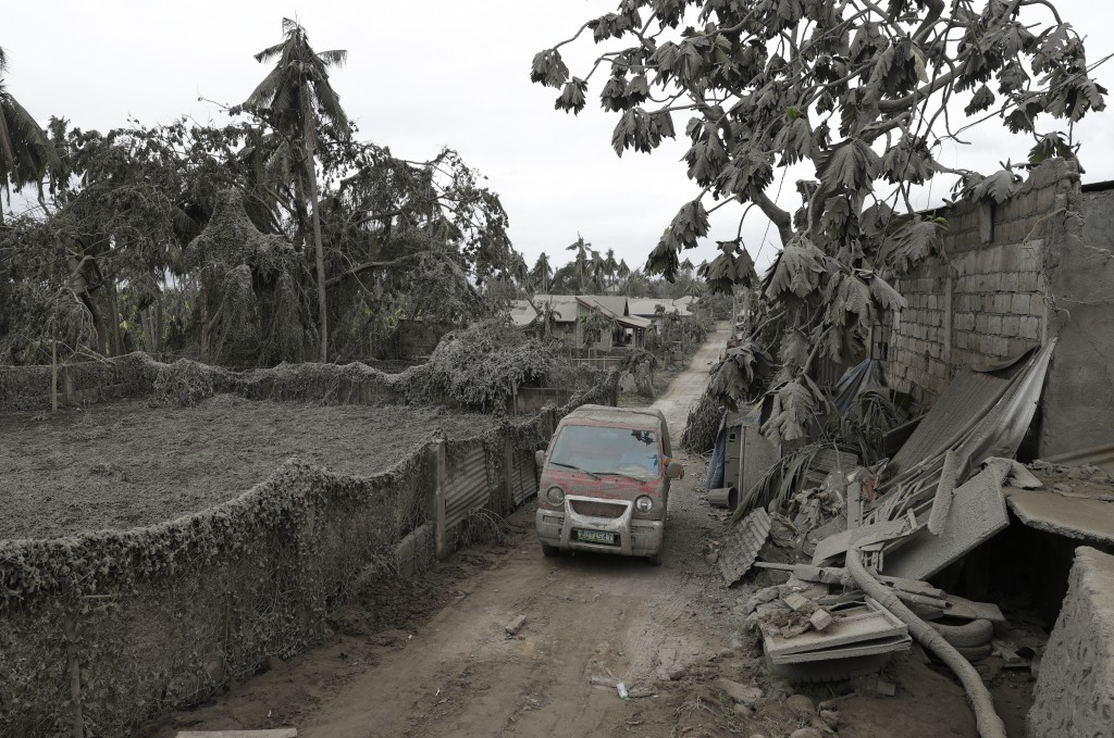 A vehicle navigates the volcanic ash covered village in Talisay, Batangas province, southern Philippines on Wednesday Jan. 15, 2020. Taal volcano is s...