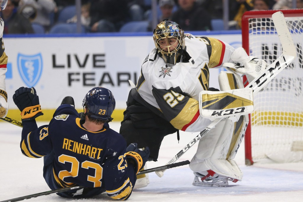 Buffalo Sabres Forward Sam Reinhart (23) and Vegas Golden Knights Goalie Marc-Andre Fleury (29) collide during the first period of an NHL hockey game ...