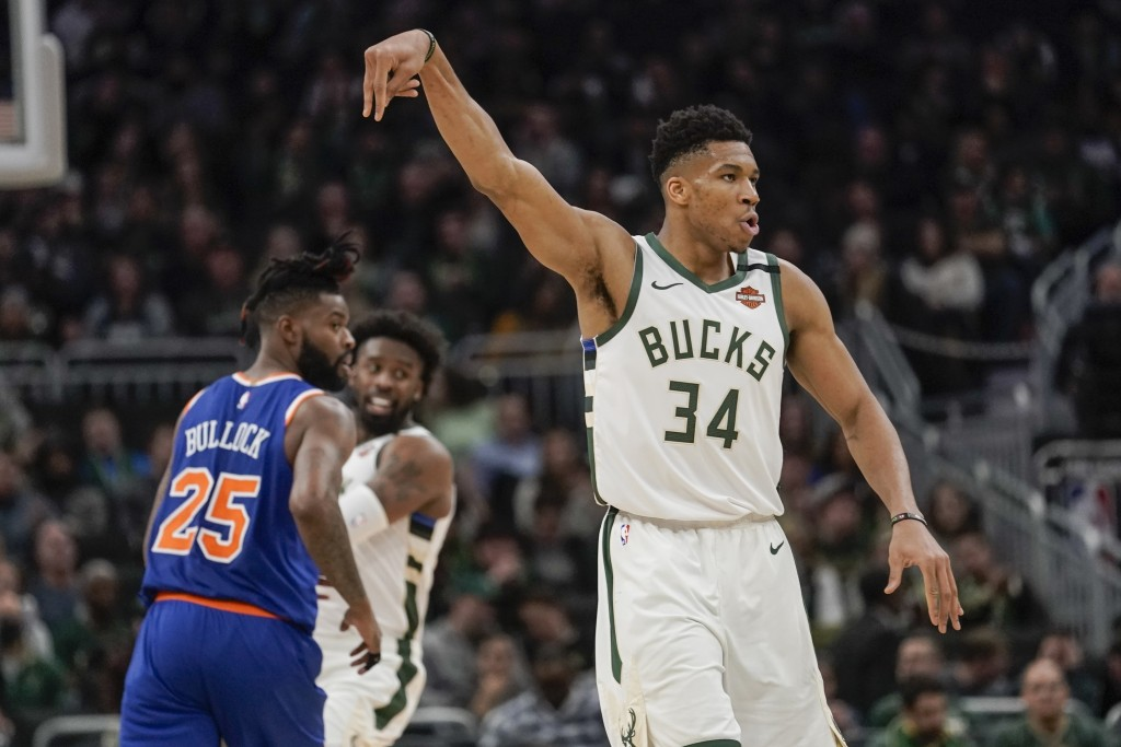 Milwaukee Bucks' Giannis Antetokounmpo reacts to his three-point basket during the second half of an NBA basketball game against the New York Knicks T...