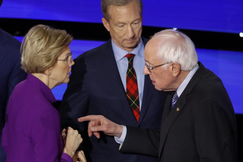 Democratic presidential candidate Sen. Elizabeth Warren, D-Mass., left and Sen. Bernie Sanders, I-Vt., talk Tuesday, Jan. 14, 2020, after a Democratic...