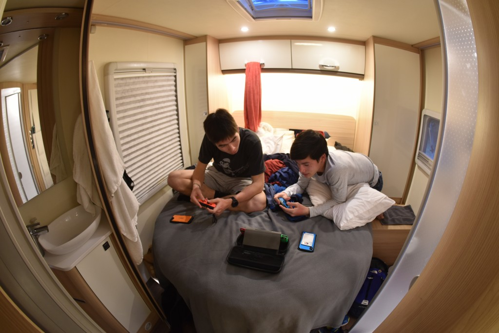 This Dec. 21, 2019, photo taken with a fisheye lens shows brothers Jacob, left, and Miles Foster gaming in the rear bedroom of their rented camper van...