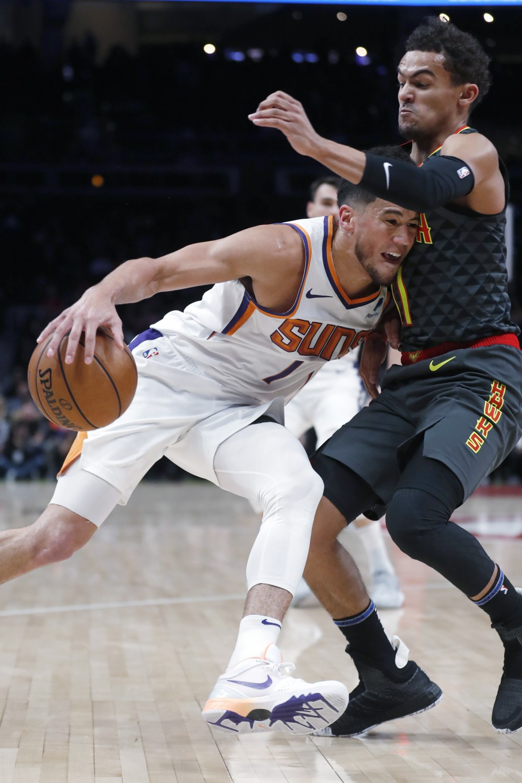 Phoenix Suns guard Devin Booker (1) drives against Atlanta Hawks guard Trae Young (11) in the first half of an NBA basketball game Tuesday, Jan. 14, 2...