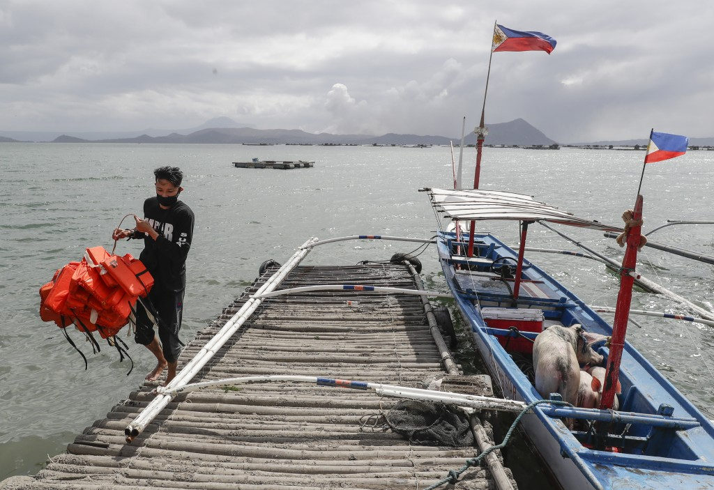 In this Jan. 14, 2020, photo, Christian Morales carries life vests beside his pigs which they rescued across the lake in Talisay, Batangas province, s...