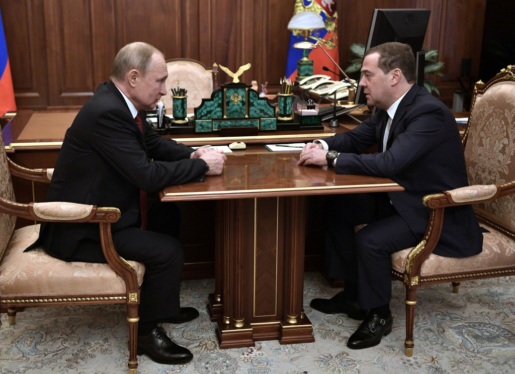 Russian President Vladimir Putin, left, listens to Russian Prime Minister Dmitry Medvedev during their meeting in the Kremlin in Moscow, Russia, Wedne...