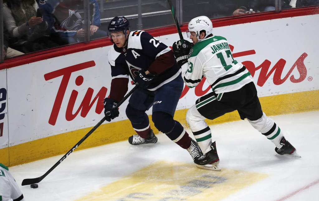 Colorado Avalanche center Nathan MacKinnon, left, looks to pass the puck as Dallas Stars center Mattias Janmark defends in the first period of an NHL ...