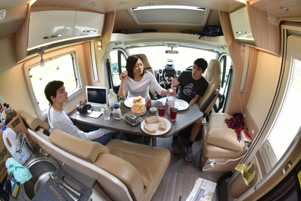 This Dec. 22, 2019, photo taken using a fisheye lens shows the Foster family eating lunch in their rented camper van at a roadside stop on the South I...
