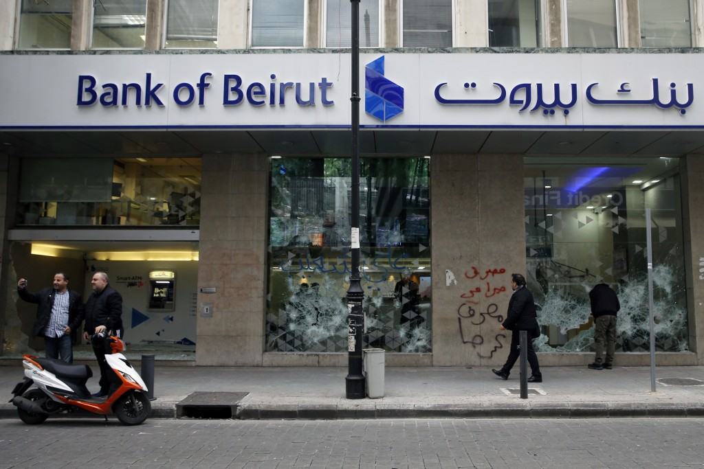 People look at the broken facade of Bank of Beirut that was smashed by anti-government protesters in Beirut, Lebanon, Wednesday, Jan. 15, 2020. Banks ...
