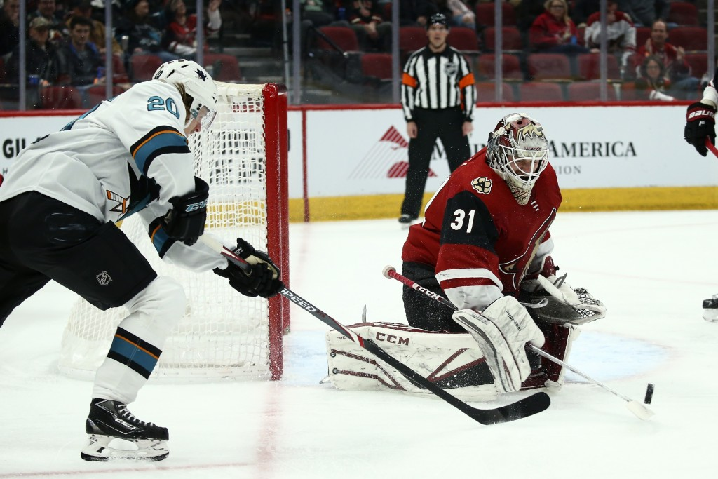 Arizona Coyotes goaltender Adin Hill (31) flips the puck away after a shot from San Jose Sharks left wing Marcus Sorensen (20) during the first period...