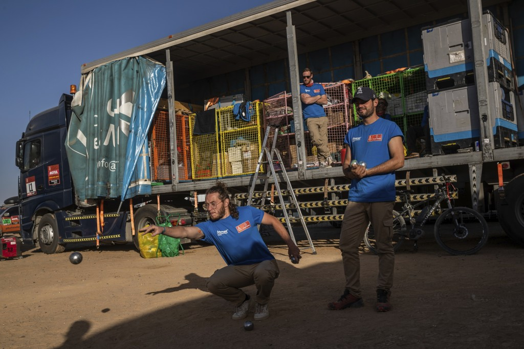 In this Monday, Jan. 13, 2020 photo, Dakar rally staffers play petanque after stage eight in Wadi Al Dawasir, Saudi Arabia. Formerly known as the Pari...
