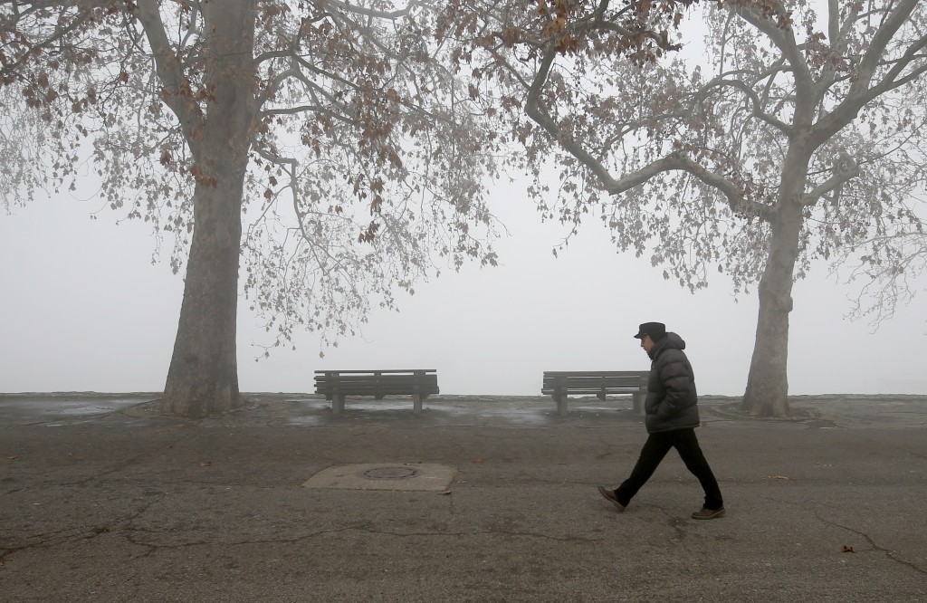 A man walks on the banks of Danube river in Belgrade, Serbia, Wednesday, Jan. 15, 2020.  Serbia's government on Wednesday called an emergency meeting,...
