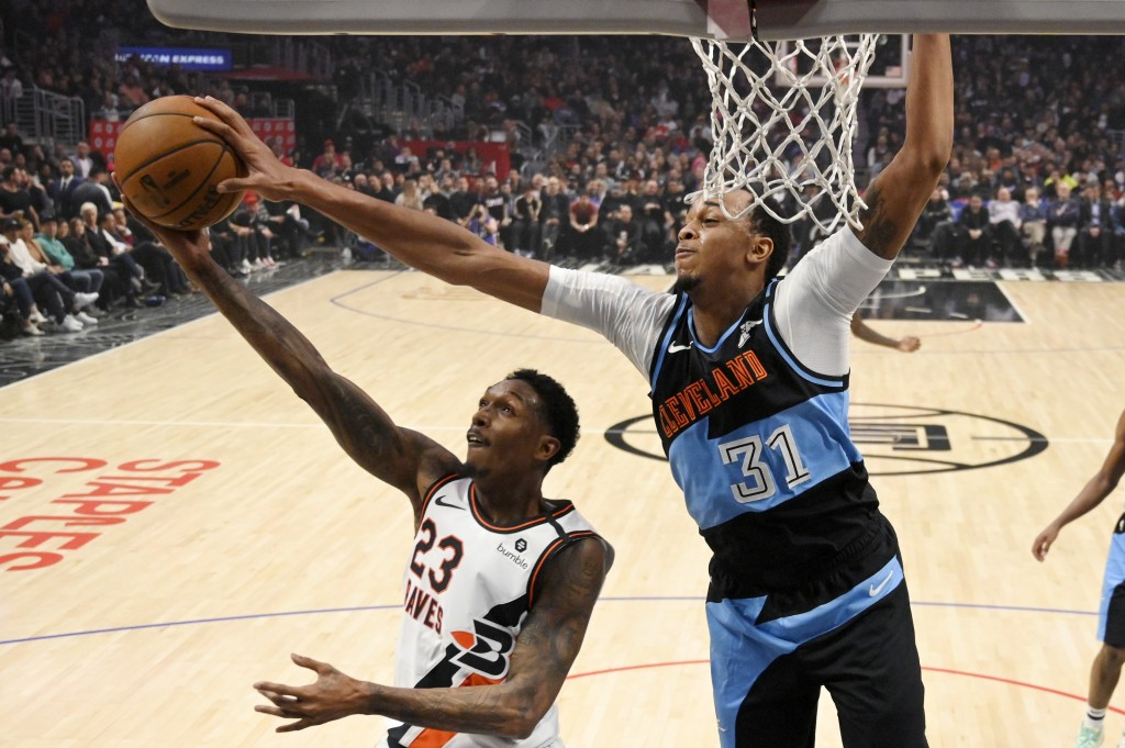 Los Angeles Clippers guard Lou Williams, left, has his shot blocked by Cleveland Cavaliers forward John Henson during the first half of an NBA basketb...