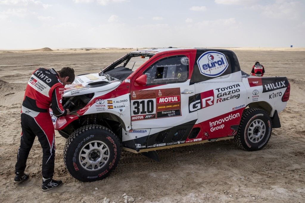 Co-driver Marc Coma, of Spain, repairs his Toyota at the end of stage ten of the Dakar Rally between Haradth and Shubaytah, Saudi Arabia, Wednesday, J...
