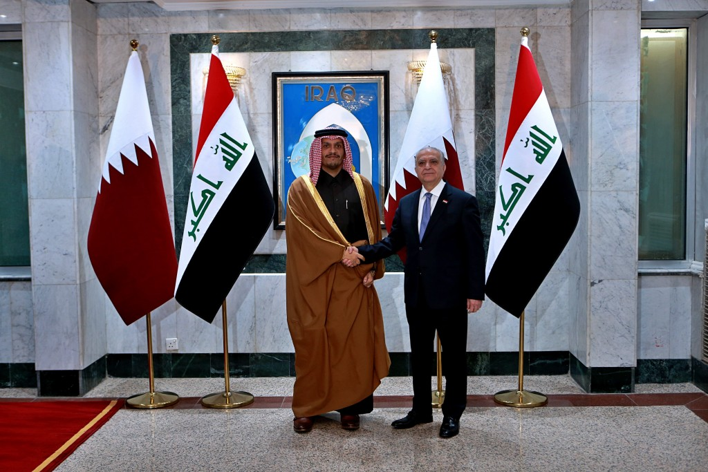 Iraqi Foreign Minister Mohamed Alhahkim, right, shakes hands with visiting Qatari counterpart Sheikh Mohammed bin Abdulrahman Al Thani in Baghdad, Ira...
