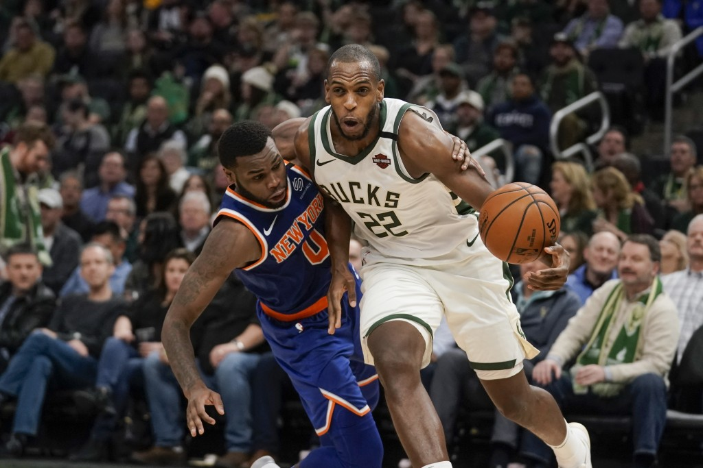 Milwaukee Bucks' Khris Middleton is fouled by New York Knicks' Kadeem Allen during the second half of an NBA basketball game Tuesday, Jan. 14, 2020, i...