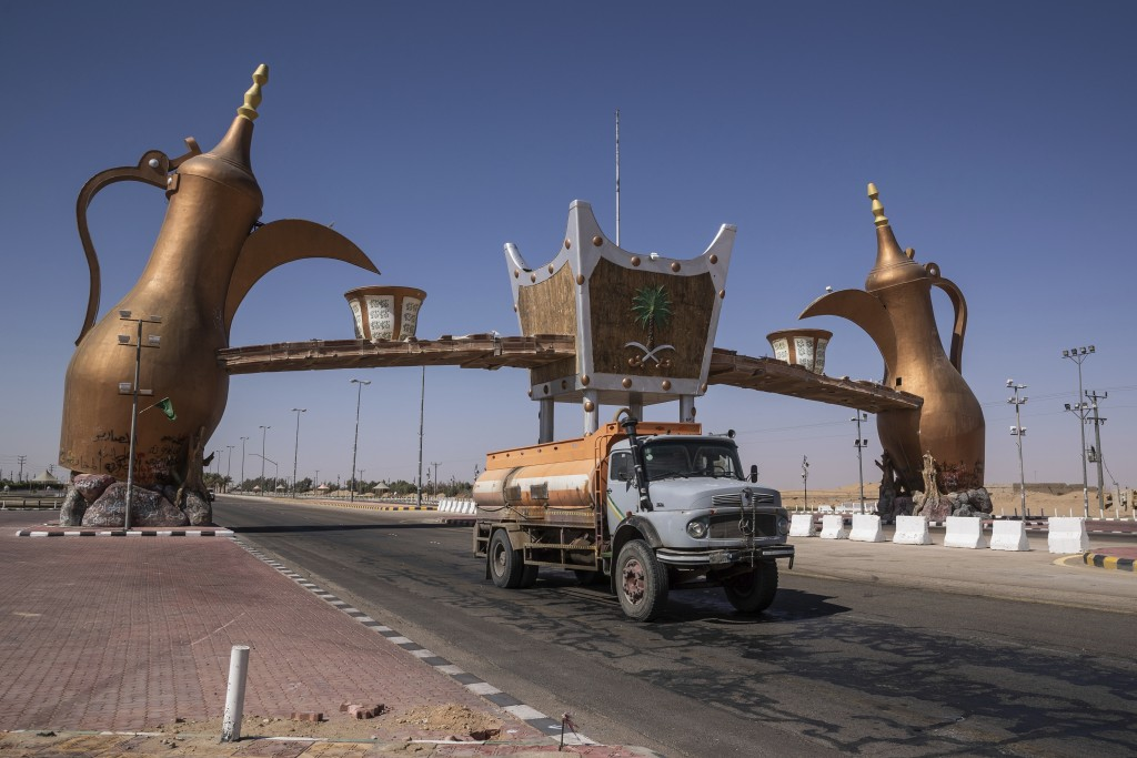 In this Monday, Jan. 13, 2020 photo, a track drives past the entrance gate of Wadi Al Dawasir, Saudi Arabia. Formerly known as the Paris-Dakar Rally, ...
