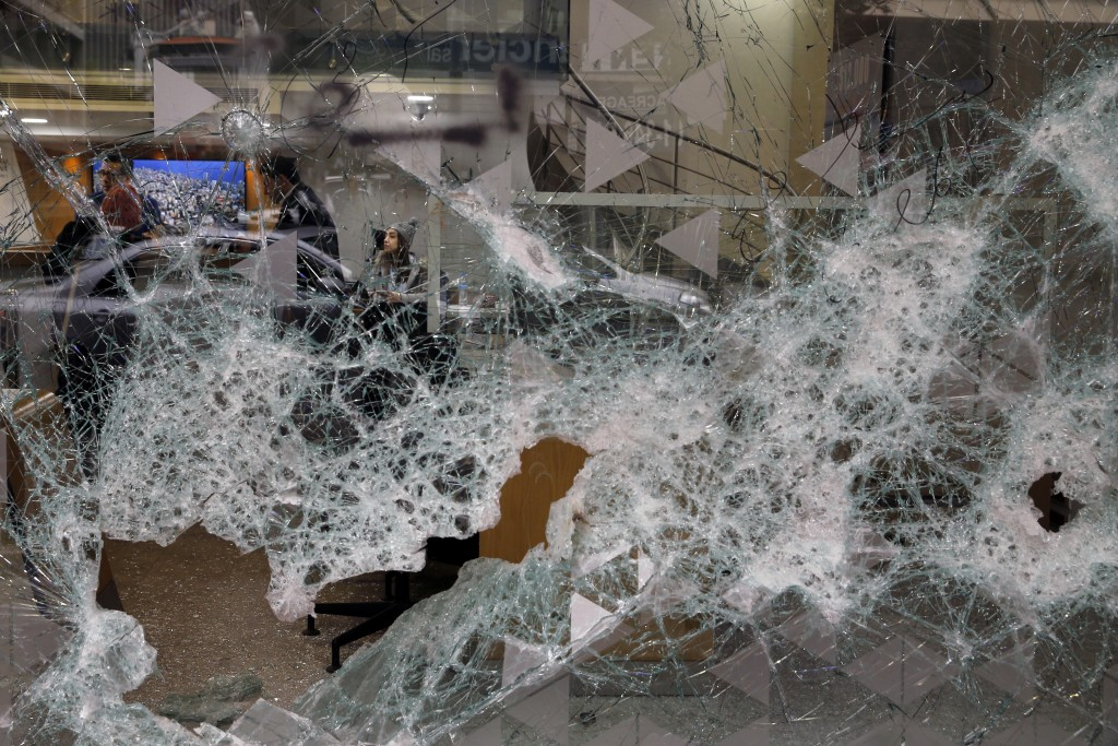 Bank employees are seen through the broken facade of Bank of Beirut that was smashed by anti-government protesters in Beirut, Lebanon, Wednesday, Jan....