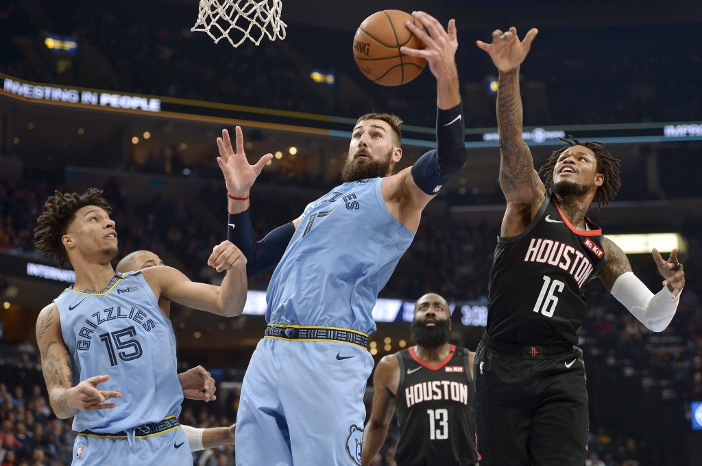 Memphis Grizzlies center Jonas Valanciunas (17) grabs the ball between forward Brandon Clarke (15) and Houston Rockets guards Ben McLemore (16) and Ja...