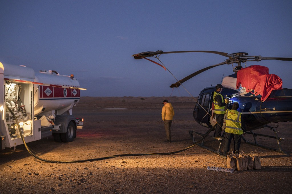 In this Sunday, Jan. 12, 2020 photo, APSCO employees fill a tank of a Dakar helicopter at the end of stage seven in Wadi Al Dawasir, Saudi Arabia. For...