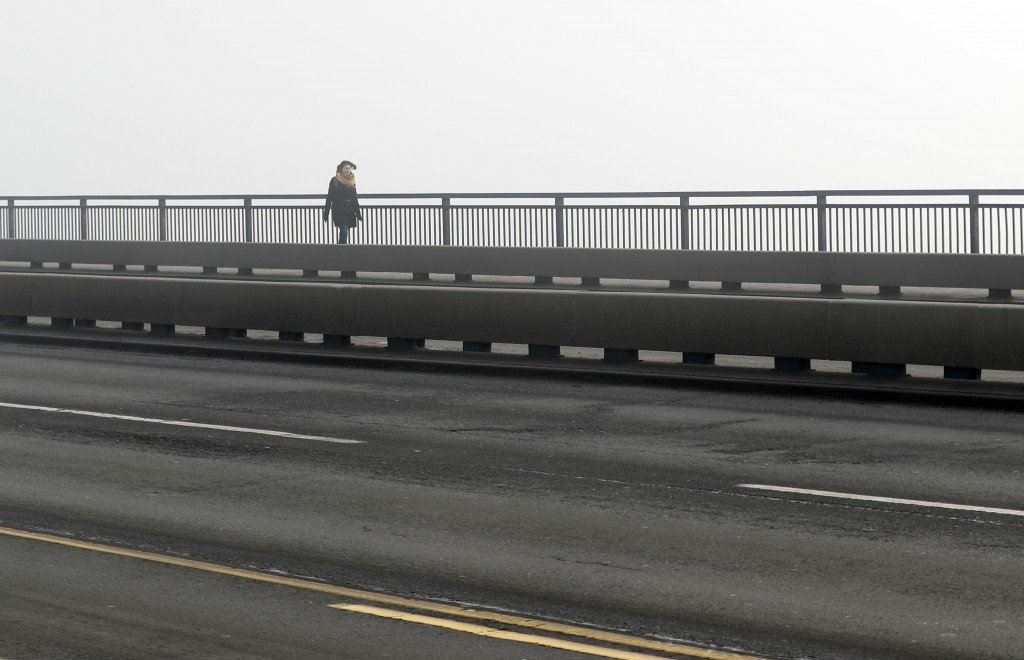 A girl walks across a bridge in Belgrade, Serbia, Wednesday, Jan. 15, 2020. Serbia's government on Wednesday called an emergency meeting, as many citi...